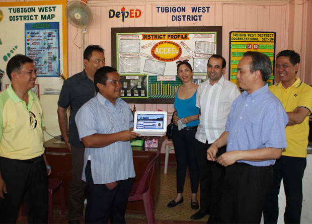 Christopher Gudia (third from left, with notebook computer), principal of Tubigon West Central School in Bohol, shows off a computer to connected to the Internet with TV White Space (TVWS). Others in the photo include DOST-ICT Office Region 7 Director Jose Bagulaya, Bohol provincial government representative Glen Doloritos, DOST ICT Office deputy executive director Bettina Quimson, Momo Karouni of IXS for All, Undersecretary Louis Casambre of the DOST-ICT Office, and Nityo Infotech managing director Roy del Rosario.