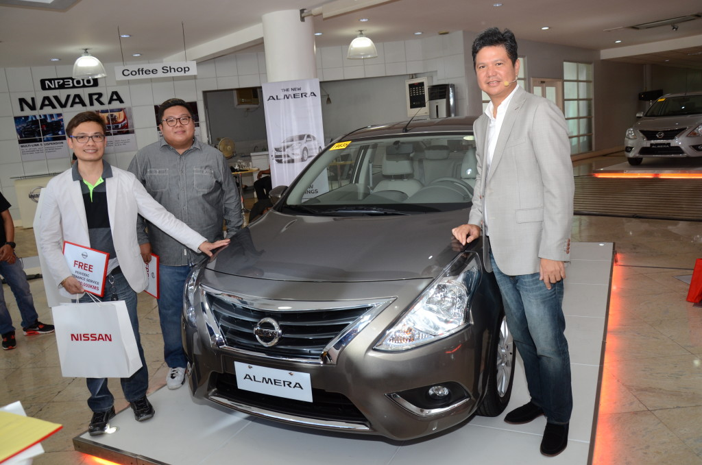 (From left) Sherex Denver Corpuz and Randall Negado, who pride themselves as owners of a Nissan Almera with Toti Zara, NPI President and Managing Director during the launch.